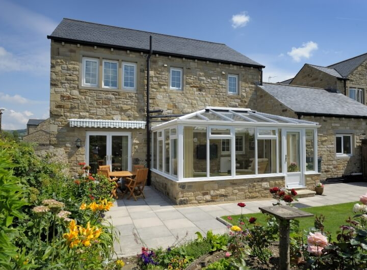 White Edwardian conservatory on a stone cottage
